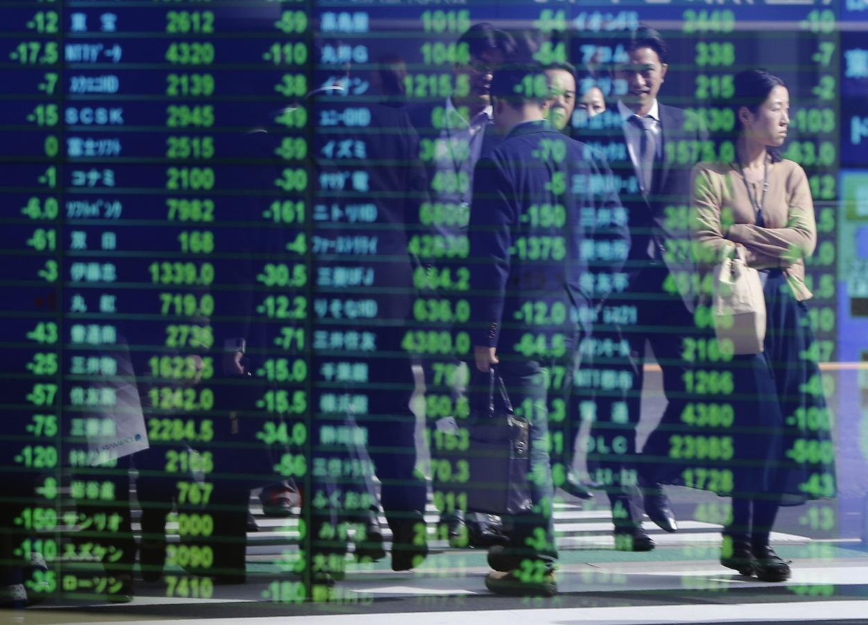Passers-by are reflected on an electronic stock quotation board outside a brokerage in Tokyo